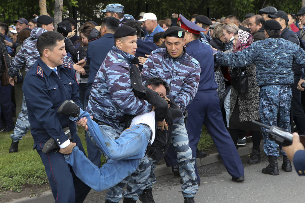 Kazakh police detain a demonstrator during an anti-government protest during the presidential e ...