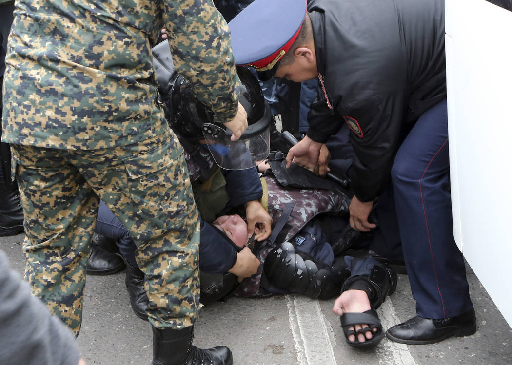 Kazakh police officers try to help their comrade during an anti-government protest during the p ...
