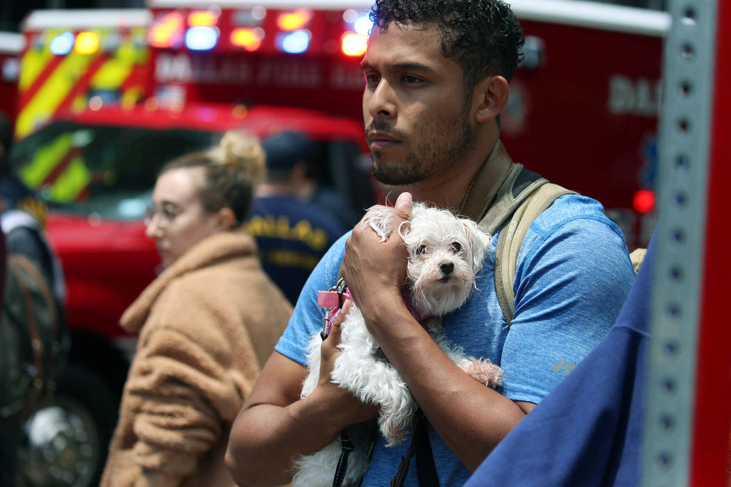 Isaiah Allen, a resident of the damaged apartments, holds onto Princess, as he watches official ...
