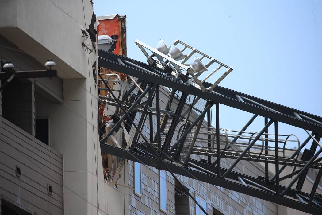 Officials respond to the scene after a crane collapsed into Elan City Lights apartments amid se ...