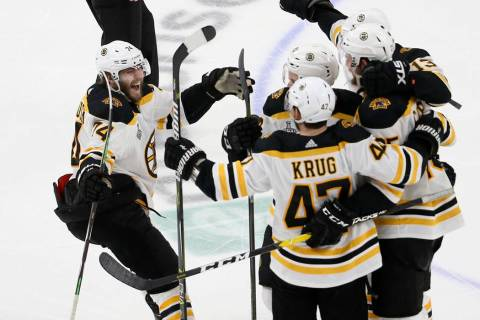 Boston Bruins left wing Jake DeBrusk (74) joins the celebration after Brandon Carlo, right, sco ...