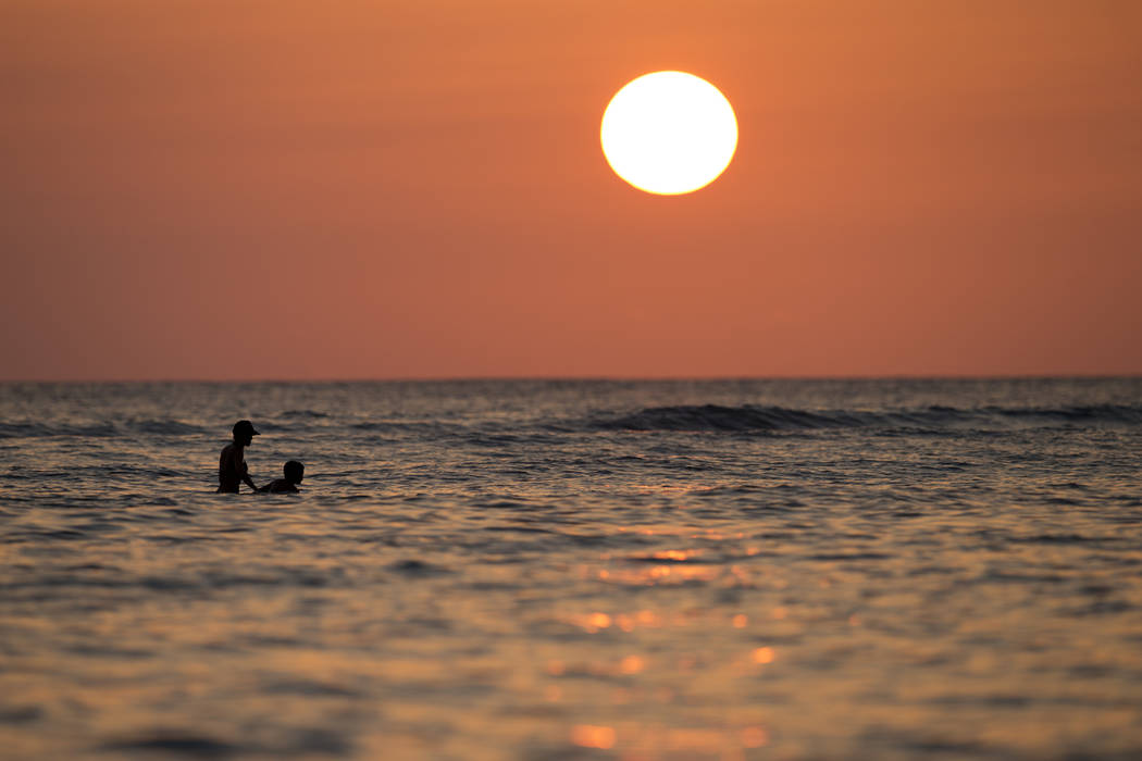 Swimmers float in the Pacific Ocean as the sun sets off of Waikiki Beach in Honolulu on New Yea ...