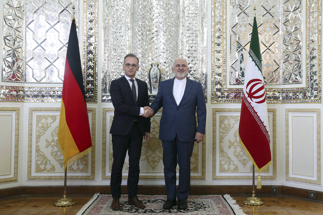 Iranian Foreign Minister Mohammad Javad Zarif, right, and his German counterpart Heiko Maas sha ...