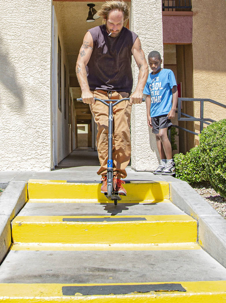 Will Hill, 30, from California, does a trick on a scooter while Devon Brown, 9, from California ...