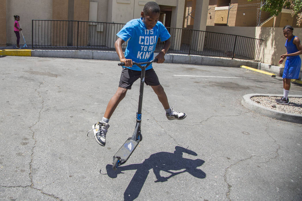 Devon Brown, 9, of North Las Vegas does a trick on his scooter during a summer day at Nellis Su ...