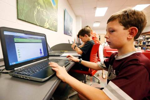 Third-grade student Miles Stidham uses an East Webster High School laptop to do homework in Mab ...