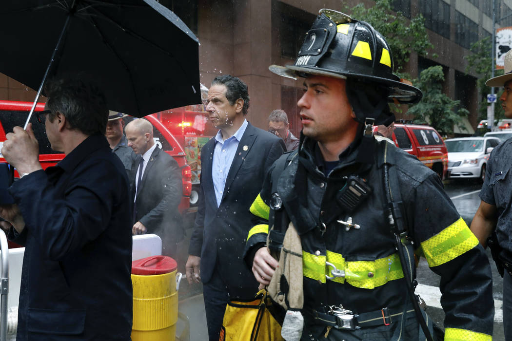 New York Gov. Andrew Cuomo, center, and first responder personnel walk near the scene where a h ...