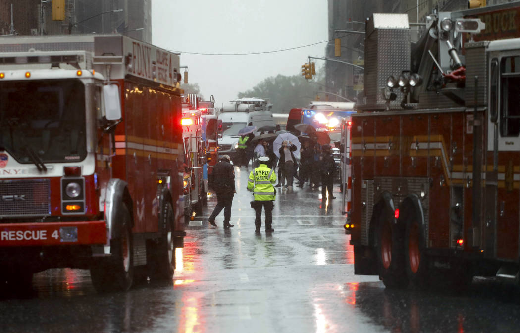 First responders arrive near the scene where a helicopter crash-landed on the roof of a midtown ...