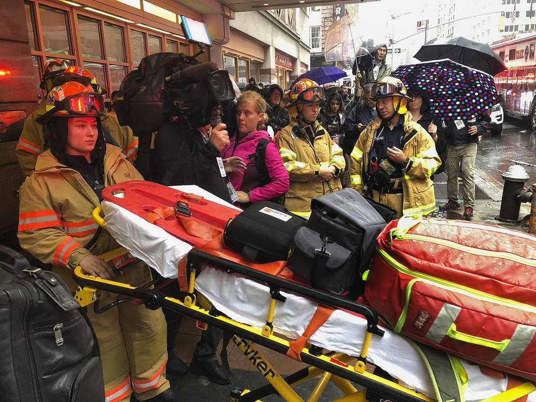 Firefighters prepare to bring a stretcher into a building, Monday, June 10, 2019, in New York, ...