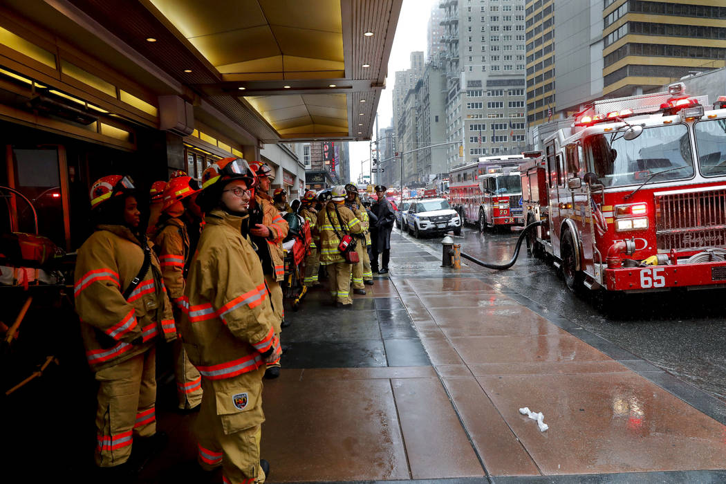 Firefighters respond to the scene where a helicopter crash-landed on the roof of a midtown Manh ...