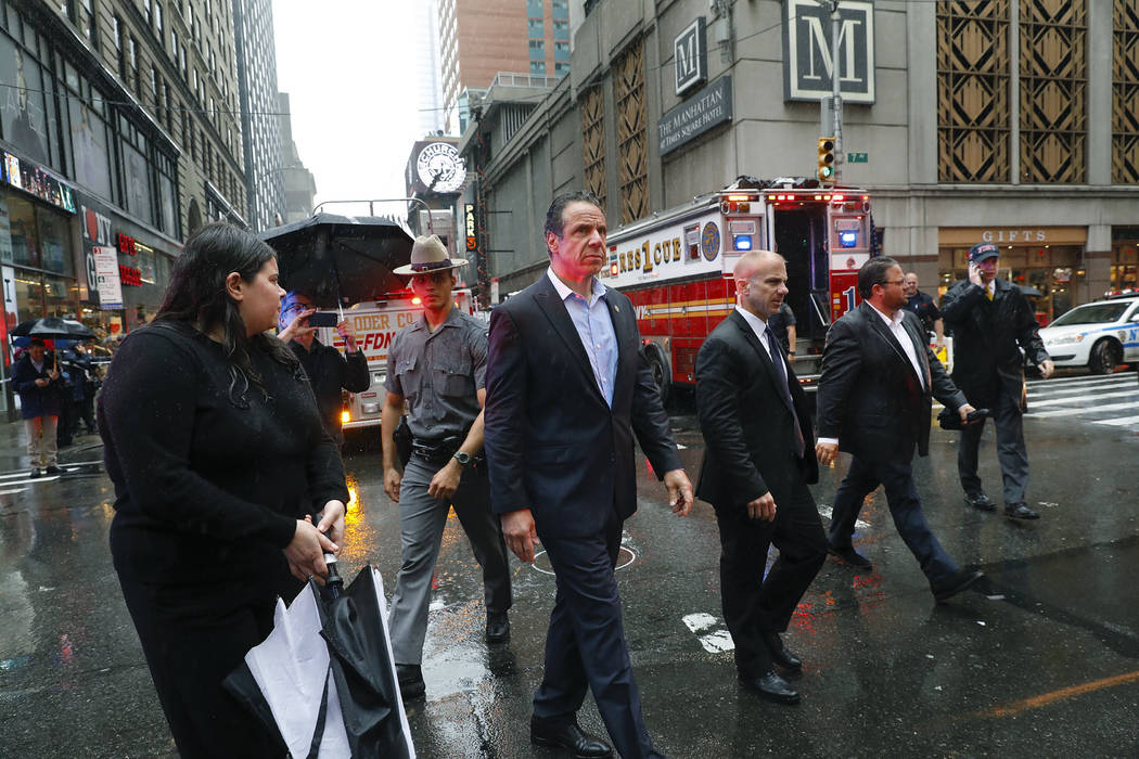 New York Gov. Andrew Cuomo, center, walks near the scene where a helicopter was reported to hav ...