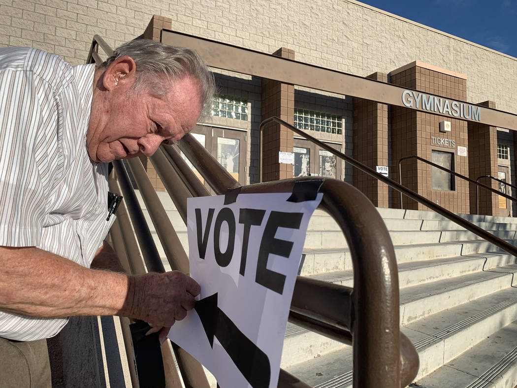 Poll worker Donald Somerville tapes up a sign for municipal elections at Bonanza High School in ...