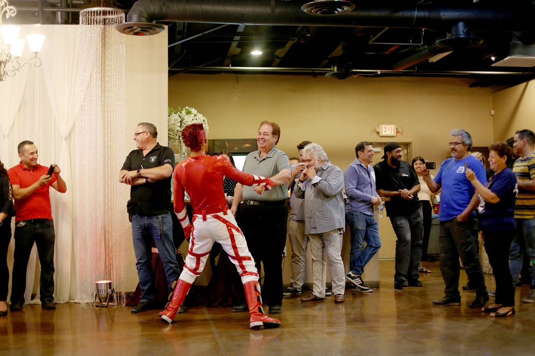 Jimmy Gonzales, a mannequin dancer, encourages Doug Rankin in the crowd at the election night v ...