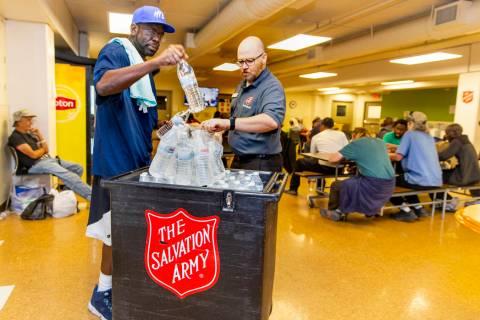 Client/volunteer Lionell Broughton assists homeless services coordinator Ryan McDonald in passi ...