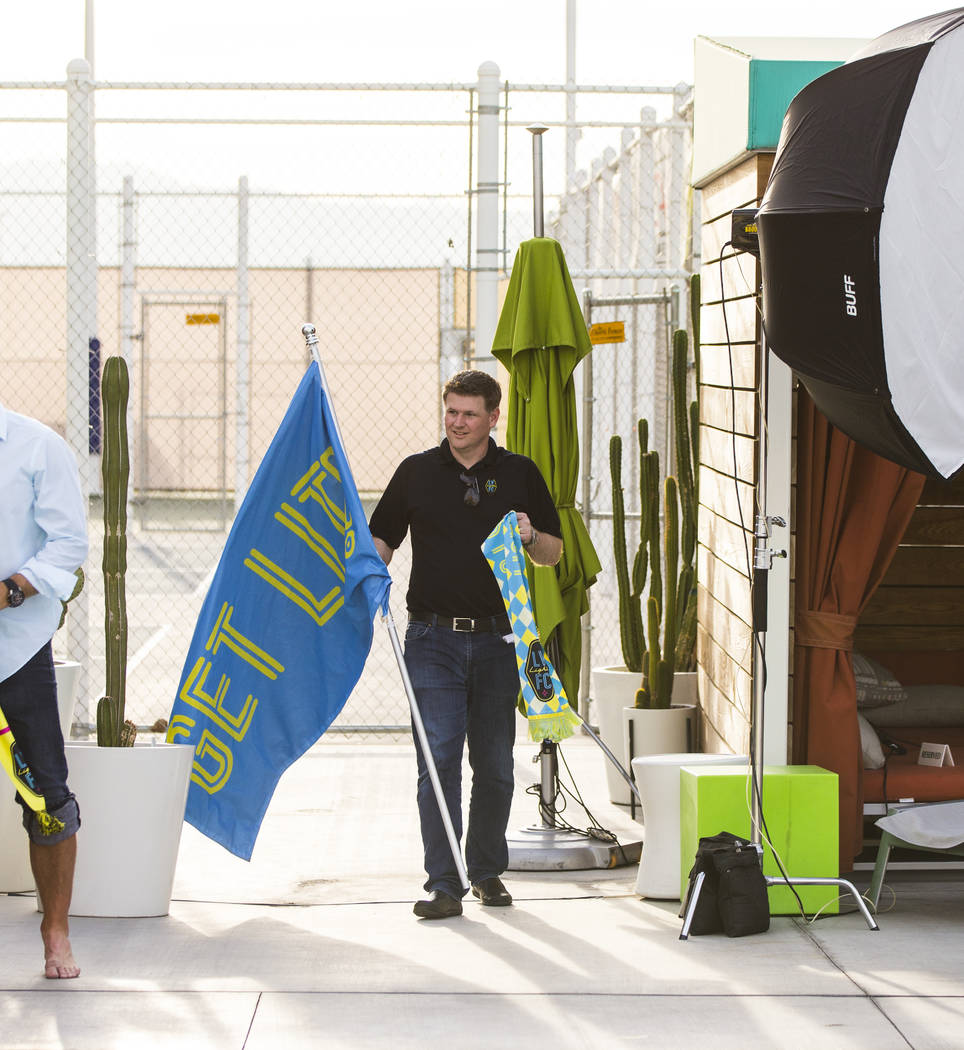 Brett Lashbrook, owner and CEO of Lights FC, walks with props while preparing for his team's ph ...