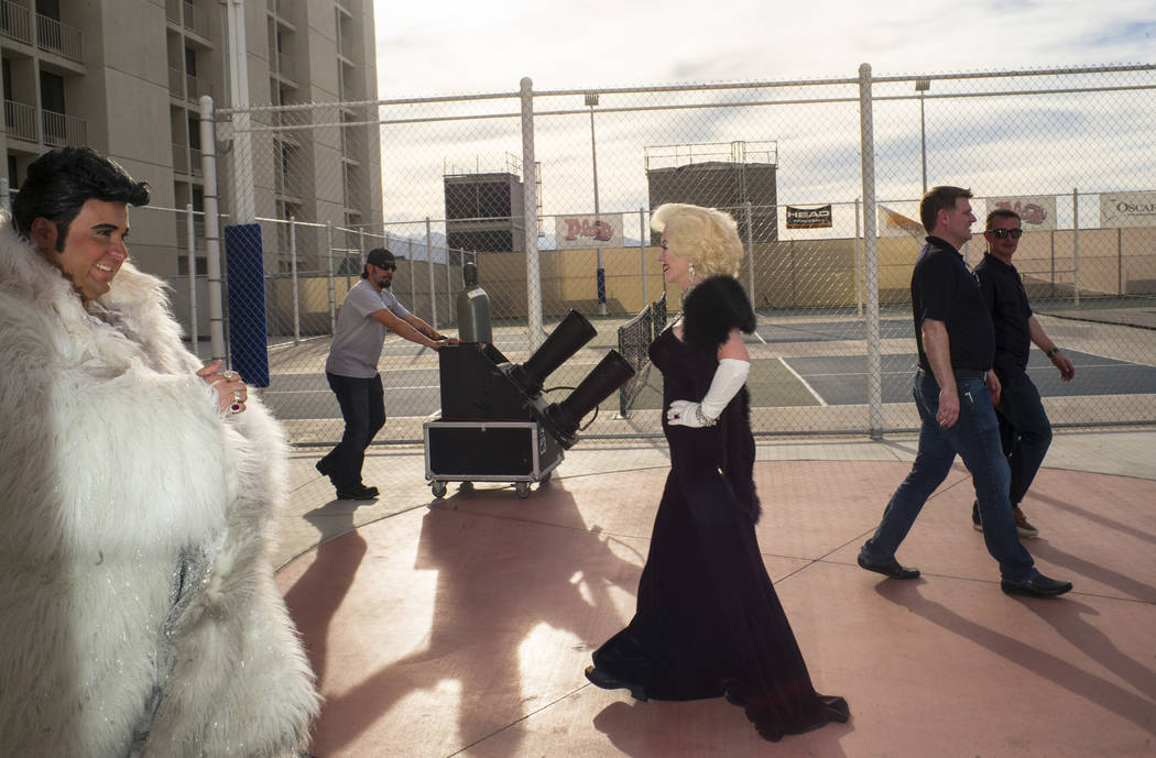 Costumed performers dressed as Liberace and Marilyn Monroe walk by a confetti cannon before the ...