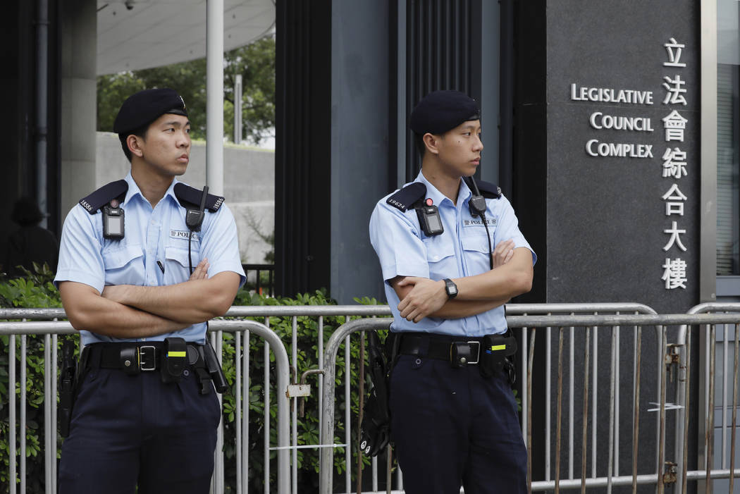 Police stand guard at fencing surrounding the Legislative Council to help block protesters duri ...
