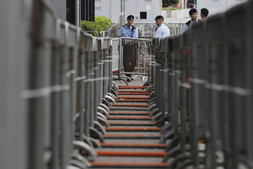 Police officers stand guard in front of barriers at the Legislative Council to prevent for stor ...