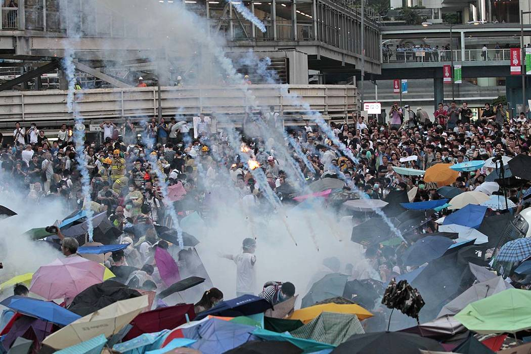 In this Sunday, Sept. 28, 2014, file photo, riot police launch tear gas into the crowd as thous ...
