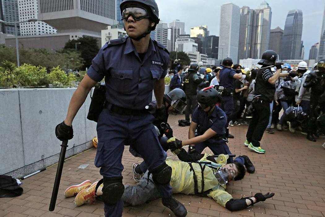 In this Monday, Dec. 1, 2014, file photo, a protester is arrested by police officers outside go ...