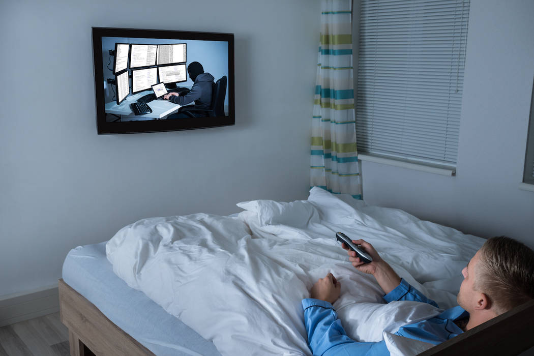 A man watches television in bed. (Getty Images)