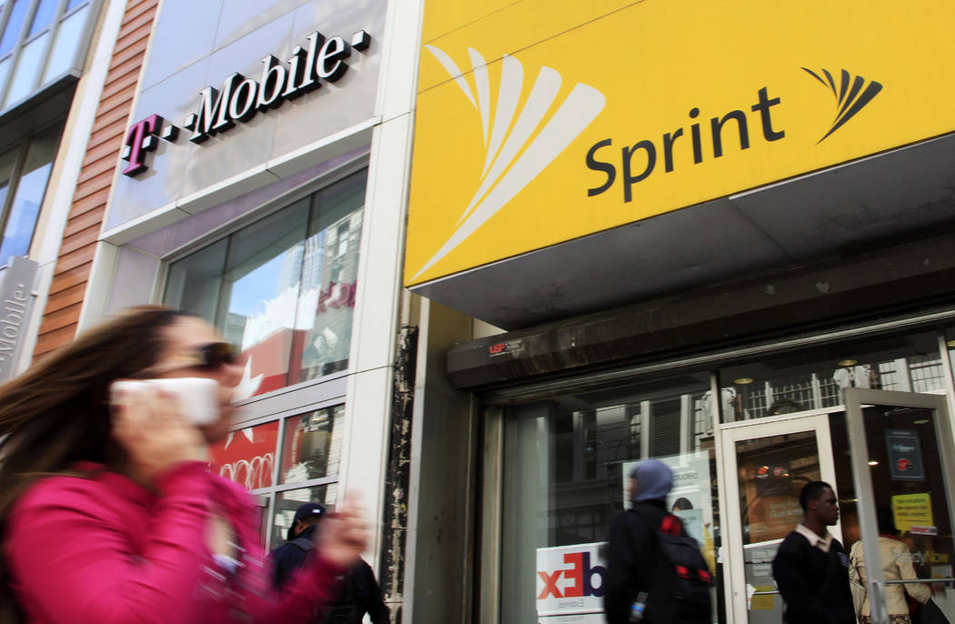 In an April 27, 2010 file photo, a woman using a cell phone walks past T-Mobile and Sprint stor ...
