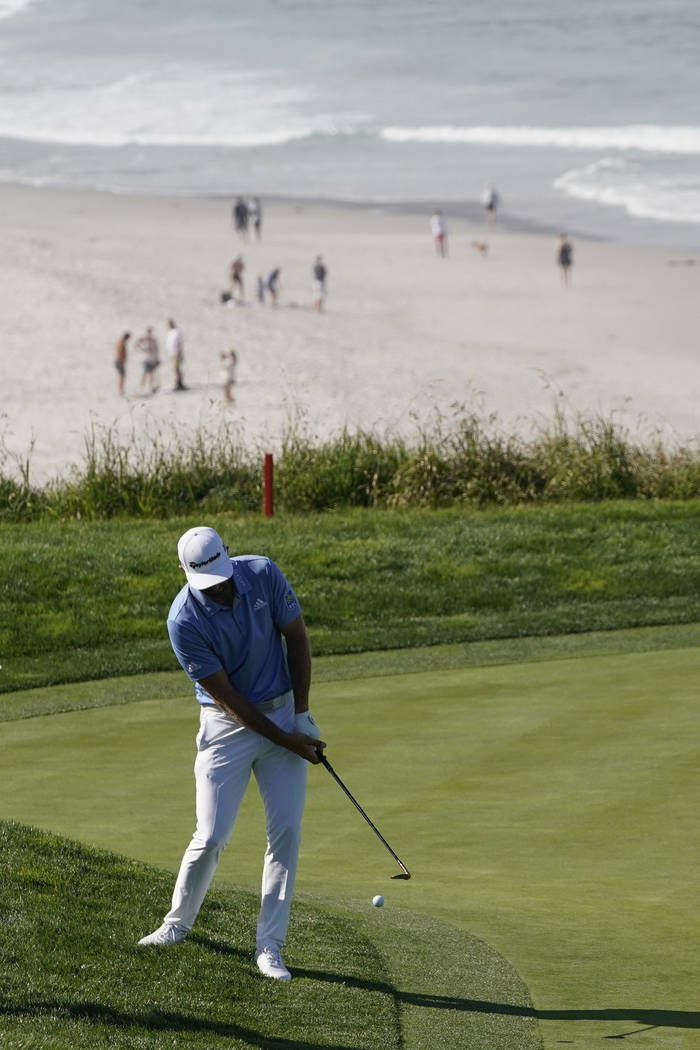 Dustin Johnson hits a chip shot on the ninth hole during a practice round for the U.S. Open Cha ...