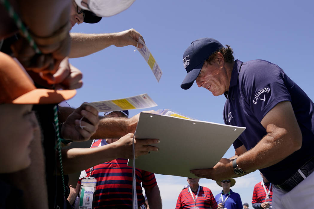 Phil Mickelson signs autographs after a practice round for the U.S. Open Championship golf tour ...