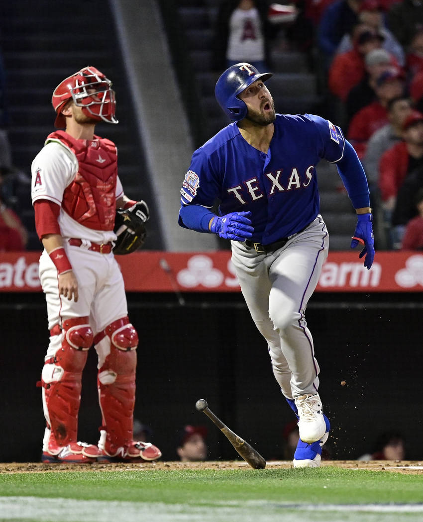 Texas Rangers' Joey Gallo heads to first on a three-run home run, next to Los Angeles Angels ca ...