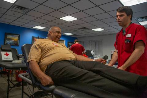 Mitchell Christensen, 28, from St. George, Utah, helps James Clark, 63, from St. Louis, left, ...