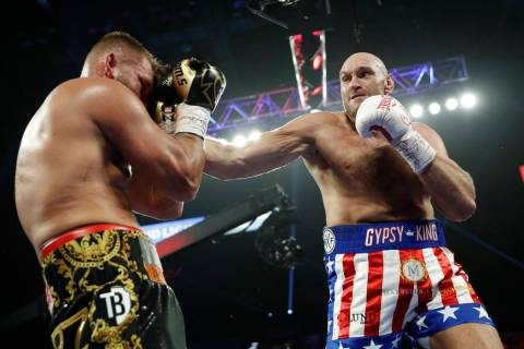Tyson Fury, of England, hits Tom Schwarz, of Germany, during a heavyweight boxing match Saturda ...