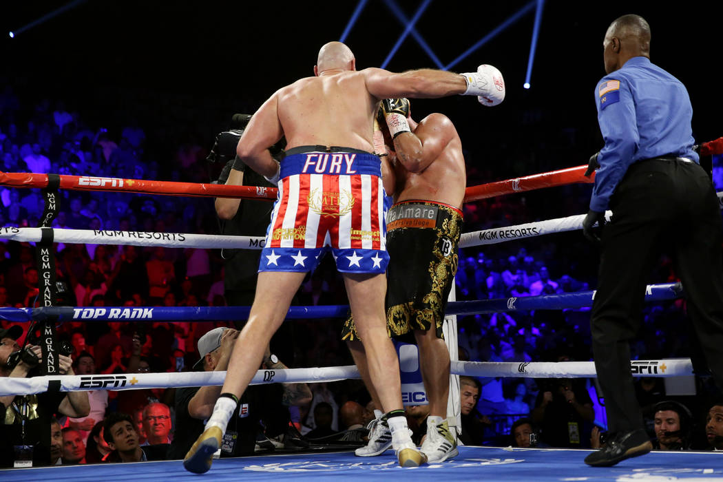 Tyson Fury, left, throws a punch against Tom Schwarz in the second round of the lineal heavywei ...