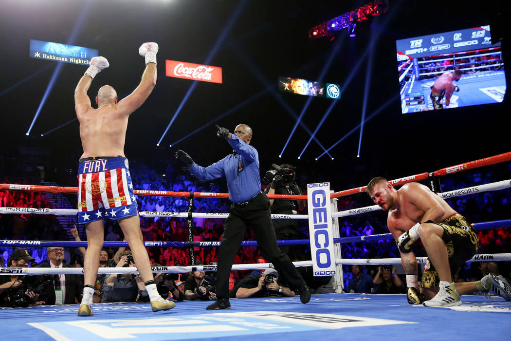 Tyson Fury, left, reacts after knocking down Tom Schwarz in the second round of the lineal heav ...