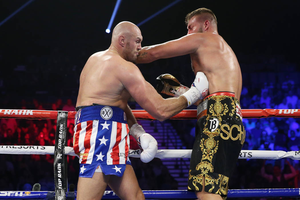 Tyson Fury, left, connects a punch against Tom Schwarz in the second round of the lineal heavyw ...