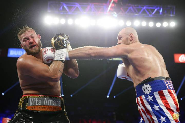 Tyson Fury, right, connects a punch against Tom Schwarz in the second round of the lineal heavy ...