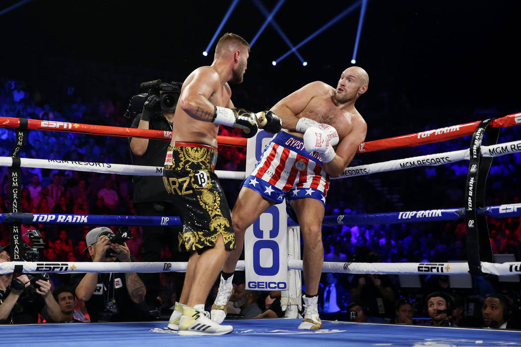 Tom Schwarz, left, battles Tyson Fury in the second round of the lineal heavyweight bout at the ...