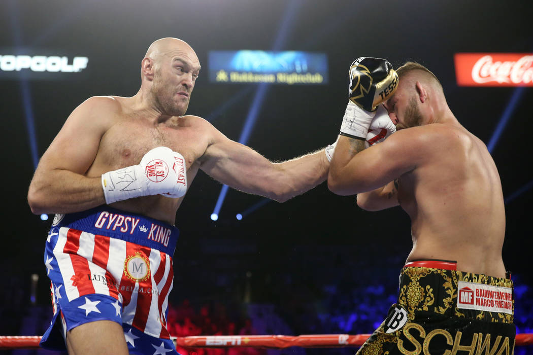 Tyson Fury, left, connects a punch against Tom Schwarz in the first round of the lineal heavywe ...