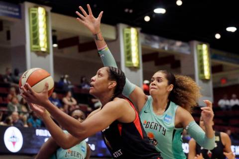 Las Vegas Aces' A'ja Wilson, left, drives past New York Liberty's Amanda Zahui B, of Sweden, du ...