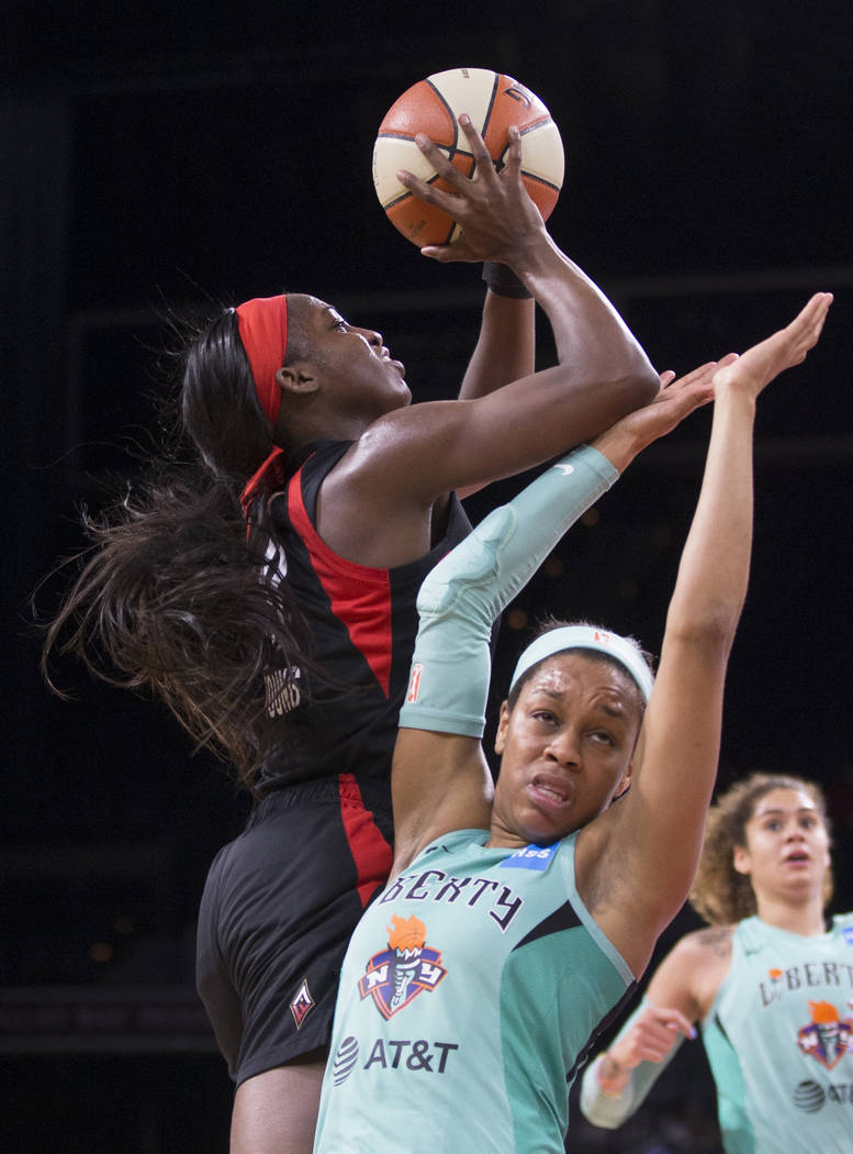 Las Vegas Aces guard Jackie Young (0) drives past New York Liberty guard Asia Durr (25) in the ...