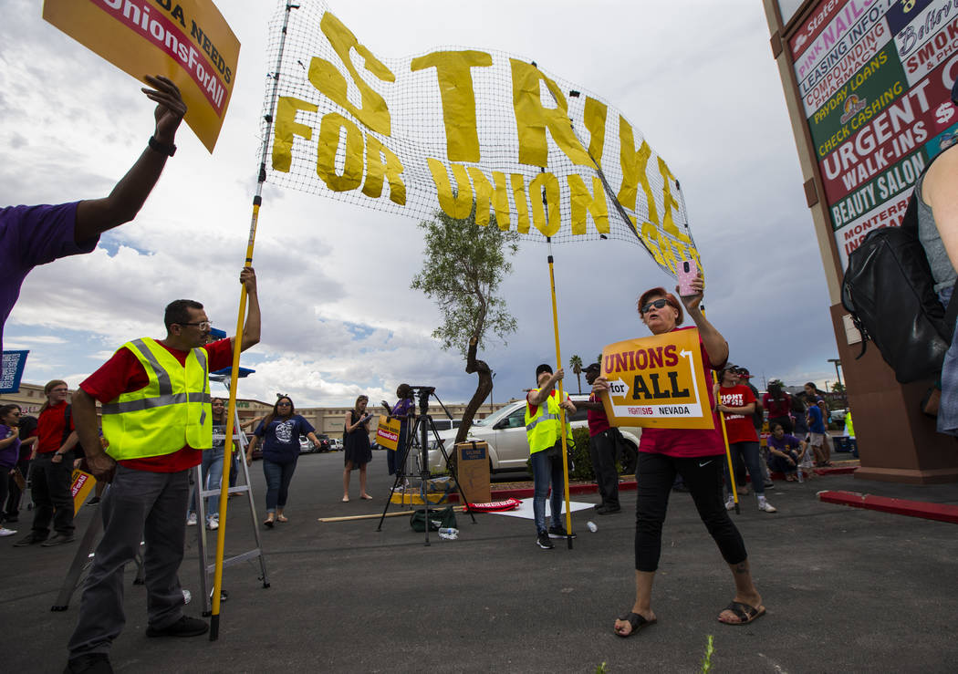 Lupe Guzman, of Las Vegas, right, holds a sign while chanting during a protest in support of hi ...