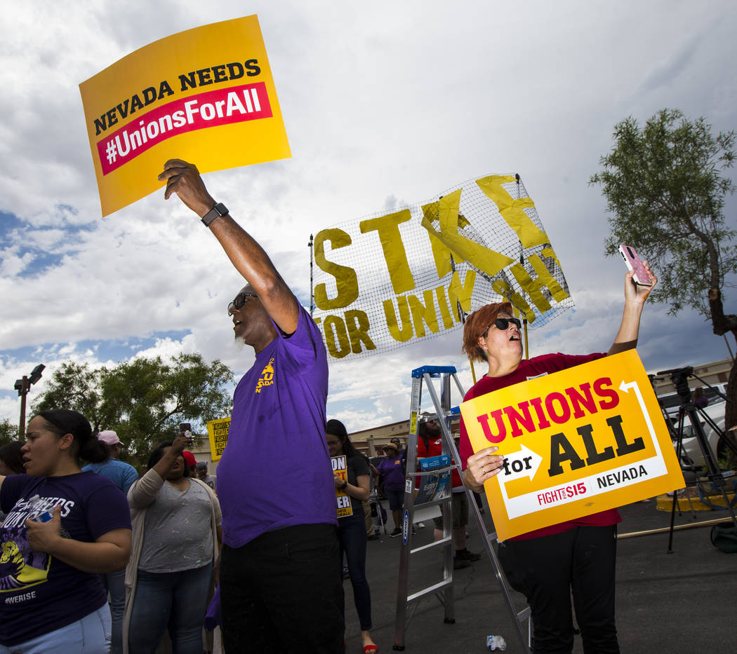 Michael Collins, left, and Lupe Guzman, both of Las Vegas, hold up signs while protesting in su ...