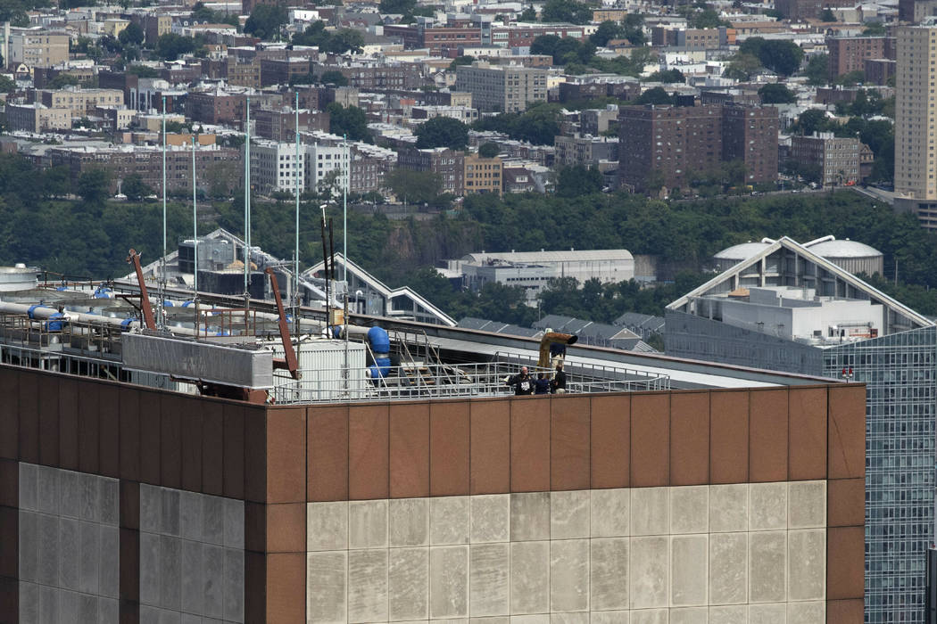 Law enforcement personnel work on the roof of the AXA Equitable building, Tuesday, June 11, 201 ...