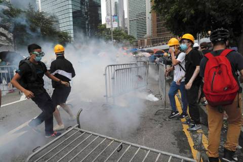 Protesters react to tear gas during a large protest near the Legislative Council in Hong Kong, ...