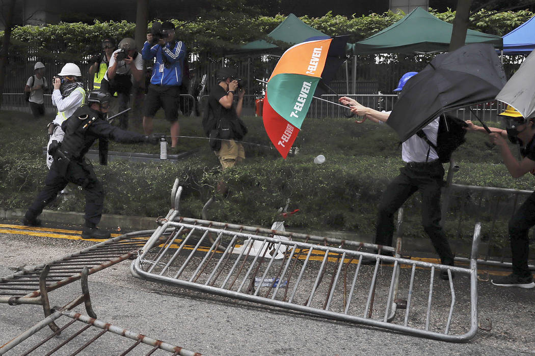 A police officer sprays pepper spray at protesters near the Legislative Council in Hong Kong, W ...