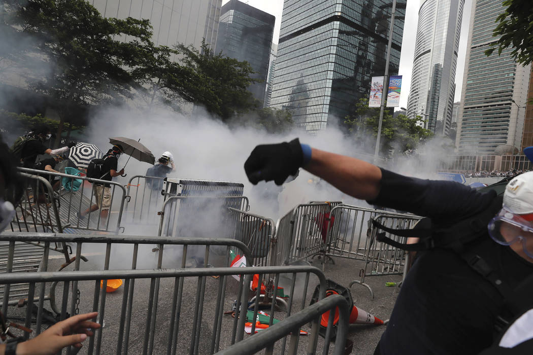 Protesters react to tear gas during a massive protest near the Legislative Council in Hong Kong ...
