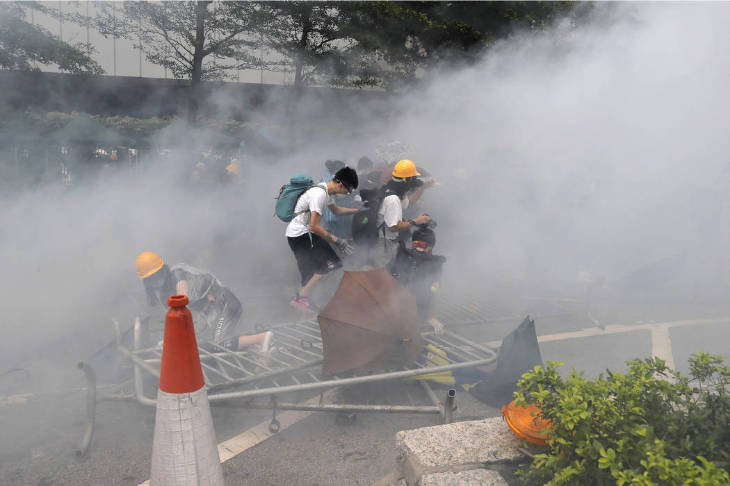 Protesters react to a cloud of tear gas near the Legislative Council in Hong Kong, Wednesday, J ...