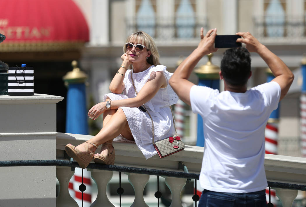 Lana Corrales poses for her husband Eric, both of Los Angeles, outside The Venetian on Friday, ...