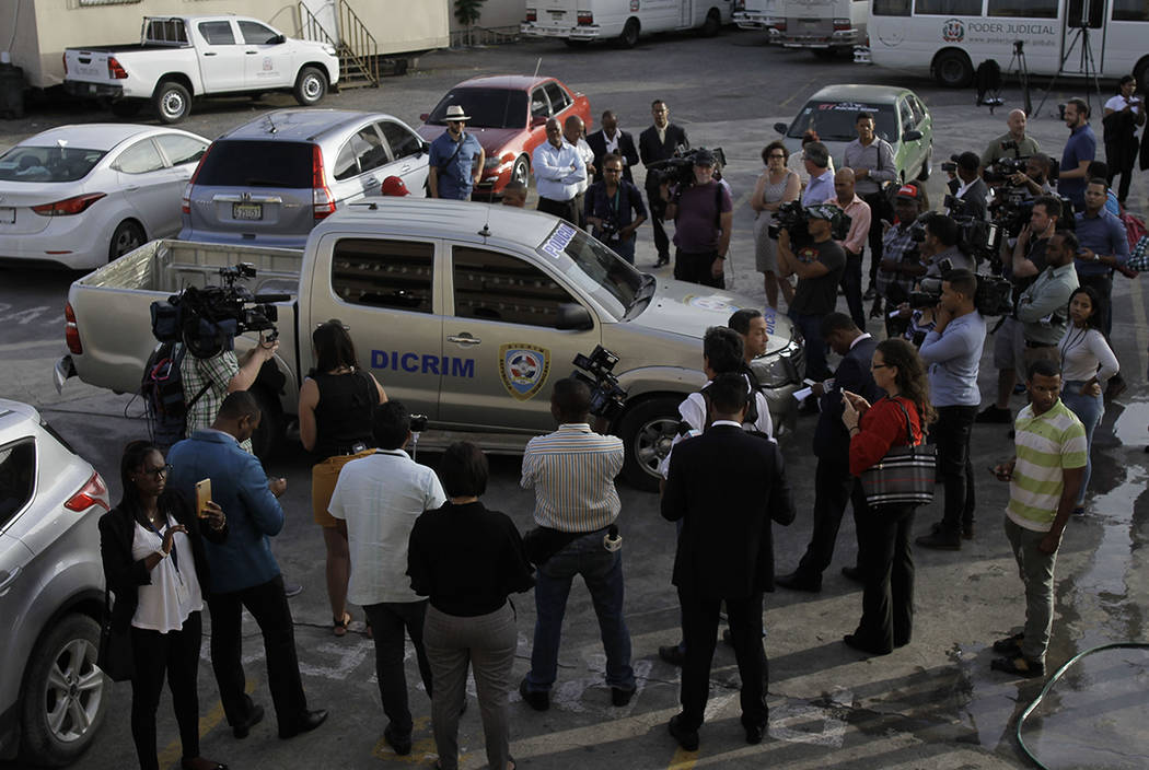Journalists surround the police vehicle carrying Eddy Vladimir Féliz Garcia who was taken ...