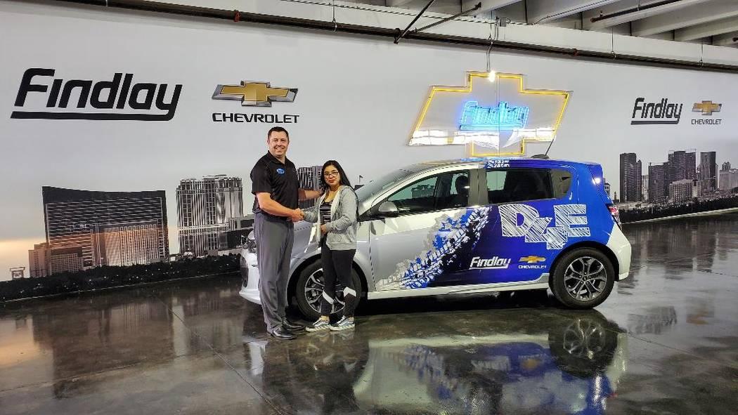 Findlay Chevrolet General Manager Doug Fleming congratulates Clark High School graduate Angela ...
