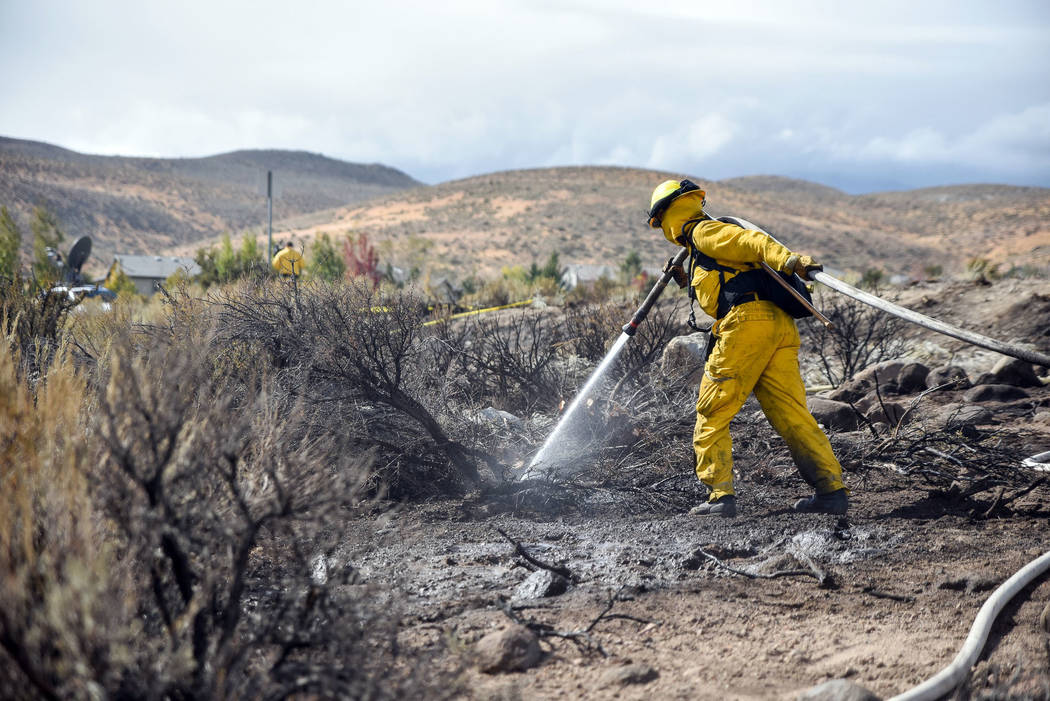 In this Oct. 14, 2016, file photo, a firefighter hoses down the area on Mount Rose Highway and ...